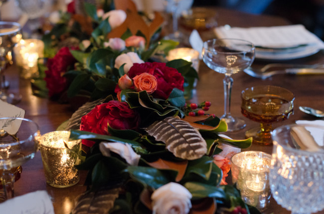 feather and rose centerpiece with candles on table