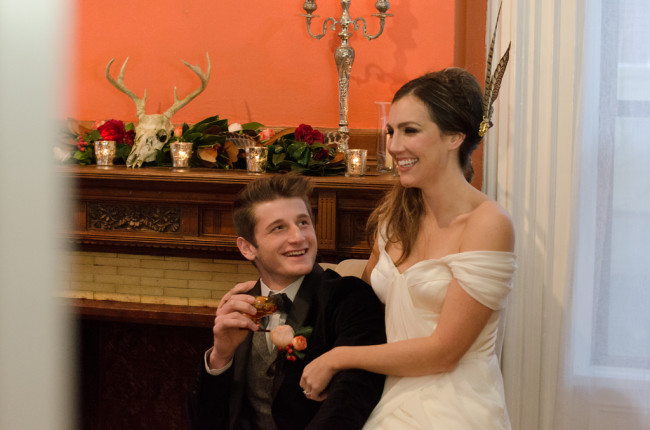 bride and groom laugh in front of fire place at Keith House in Chicago