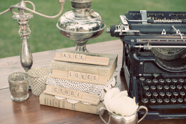 vintage chic wedding deocr: typewriter, silver candelabra, old books with scrabble tiles