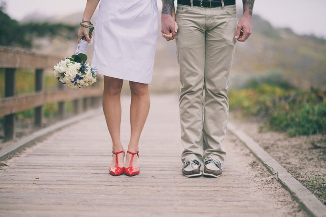 Bride and groom standing together. Red shoes and white and blue flower bouquet