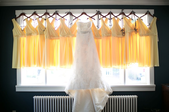 Bride's Wedding Dress hanging in front of yellow briddesmaid dresses