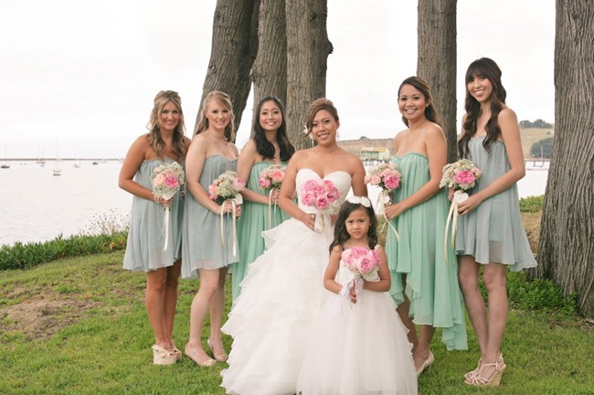 Bride with bridal party in front of lake in blue and green dresses