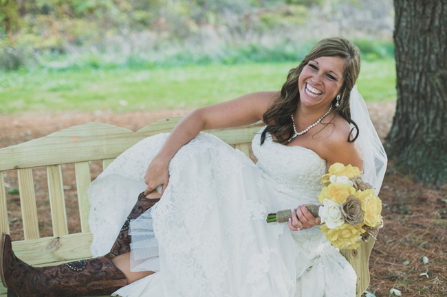 laughing bride sitting on a bench to showoff her cowboy boots