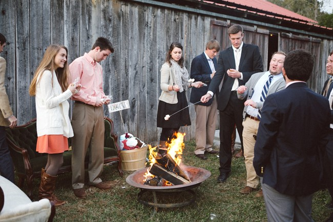 Wedding guests stand around fire pit