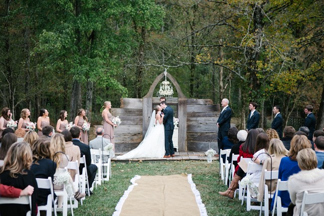 Bride and groom kisses at handmade alter