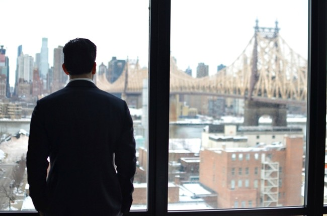 groom looking out window at Queensboro Bridge in New York