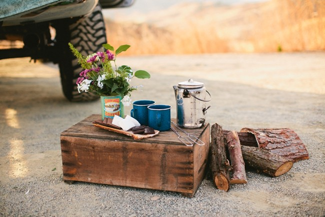 Stack of wood with hot chocolate and vase of flowers with truck behind