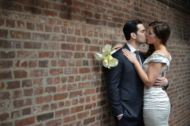 bride and groom kiss against red brick wall at The Foundry in New York