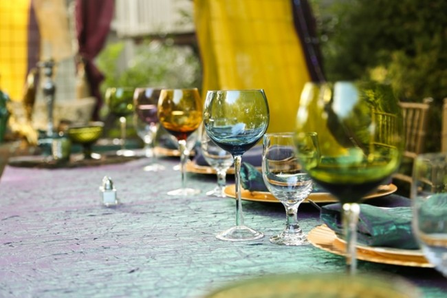 multi colored wine goblets on the table place setting
