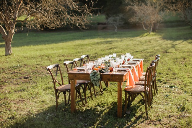 outdoor wood reception table with eight wood chairs in field