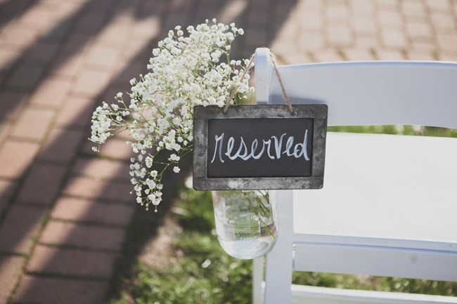 chalboard sign says 'reserved' hanging on the back of a foldup white ceremony chair