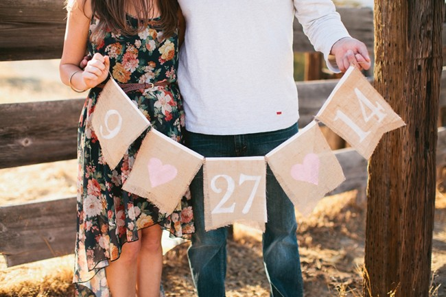 Couple holding a rustic save the date sign