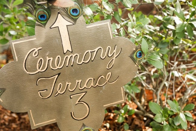 Sign to the ceremony terrace, adorned with peacock feathers