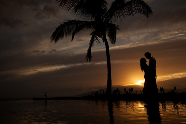 sunset with bride and groom standing next to palm tree silhouette at Hale Ko'olani