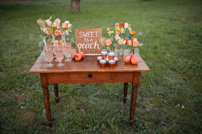 wood table on grass with peach jam, peaches, and flowers