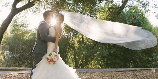 bride and groom kiss with sun in backdrop, cathedral veil catches the wind and extends out