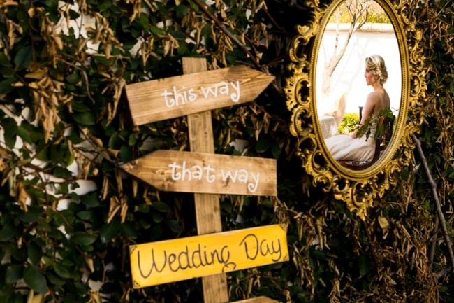 "Gold mirror with bride's reflection next to Alice in wonderland style wood arrow sign with ""This way"" and ""that way"""