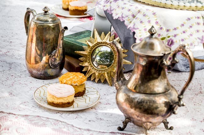 Silver teaset and dessert on doily tablecloth for Alice in Wonderland styled shoot