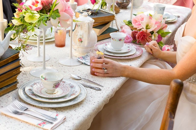 Styled shoot Alice holding spiked tea with bramble glass and sitting at table