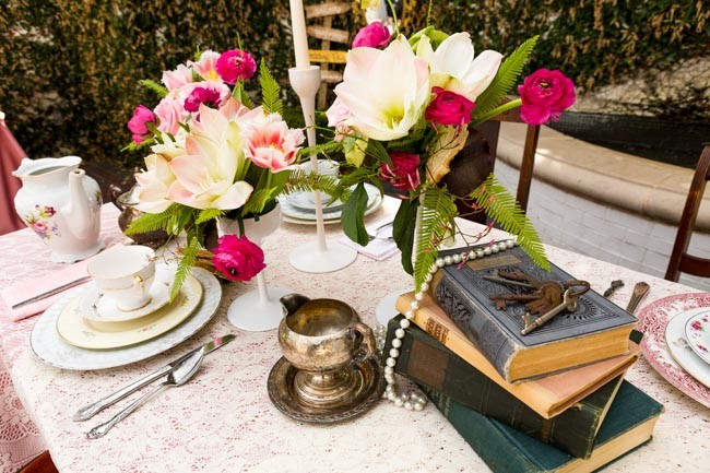 Flower displays with old books, set of keys, and string of pearls on table for Alice in Wonderland styled shoot