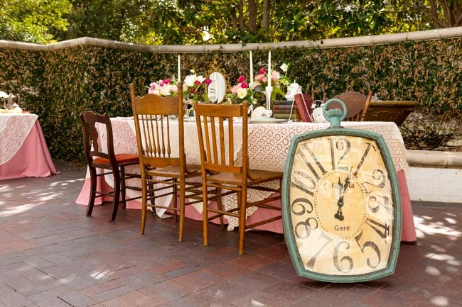 Alice in Wonderland styled shoot giant windup clock resting against table set in Arlington Hall at Lee Park