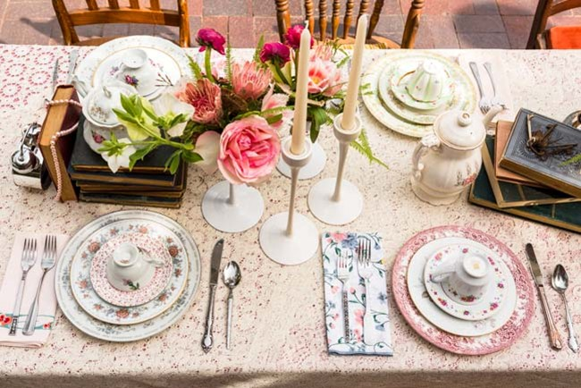 Overhead photo of table set Alice in Wonderland style (teacups, teapot, roses, books, candlesticks)