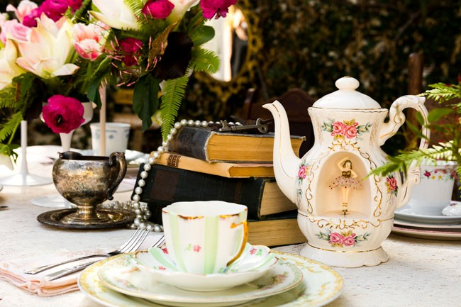 Vintage teapot and teacup with books on table