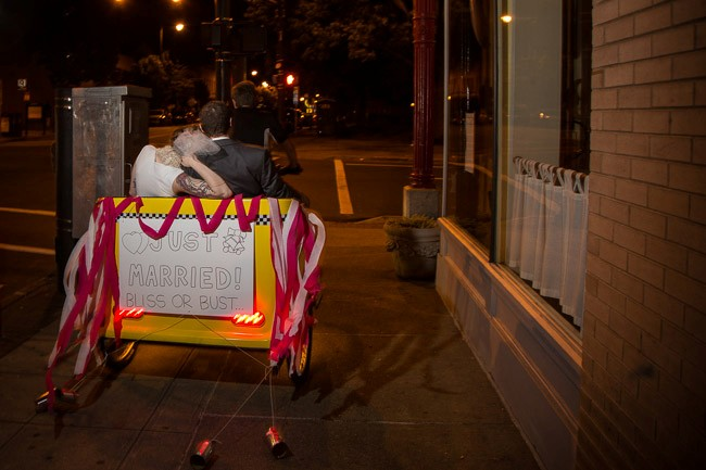 Bride and groom being driven away in a cycle rickshaw with a just married sign