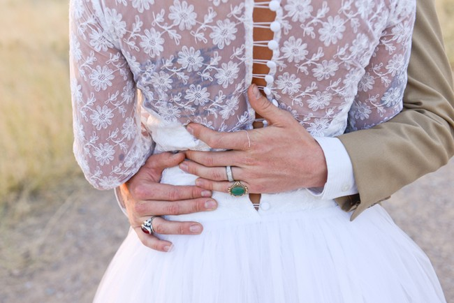 Bride in a white embroidered wedding dress with grooms arms wrapped around her