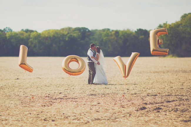 Bride and groom kiss behind gold metallic balloons in letters LOVE