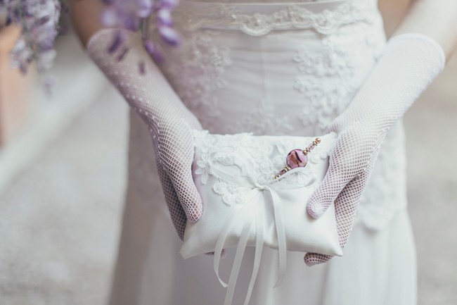 Bride holding ring pillow with white gloves