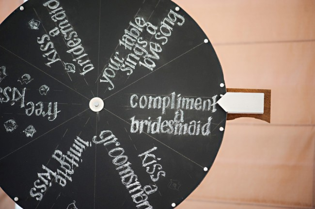 circular chalkboard spinner with kissing games for bride and groom and wedding party