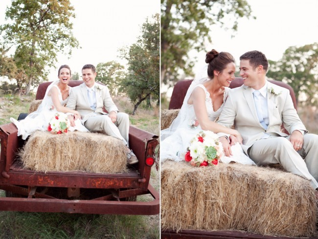 Bride and groom in back of a truck with hay