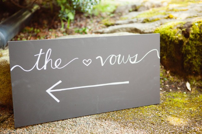 square chalkboard sign with an arrow pointing to the vows at a wedding