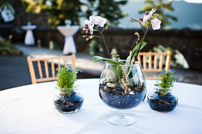 glass bowl with rocks and flowers centerpiece