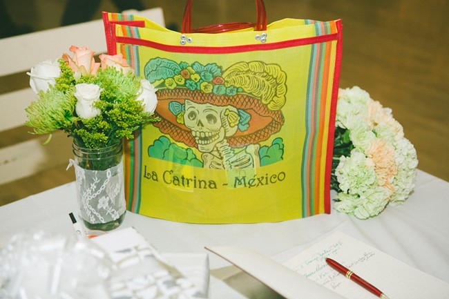 A Mexico la catrina bag with two bouquet of white and pink flowers