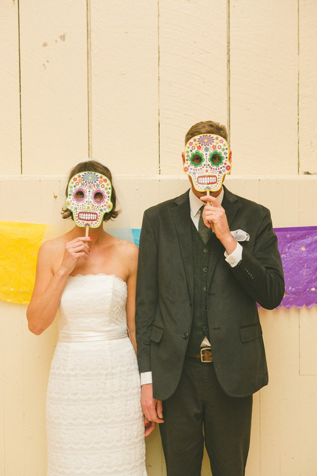 Bride and groom wearing Mexican day of the dead skull masks