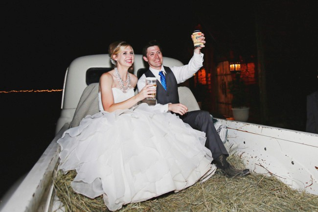 Bride and groom in back of truck with hay