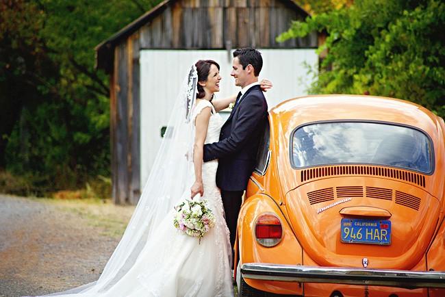 Bride and groom standing beside and orange Volkswagen bug
