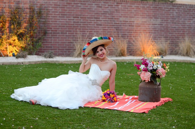 bride sitting on picnic blanket wearing a sombrero