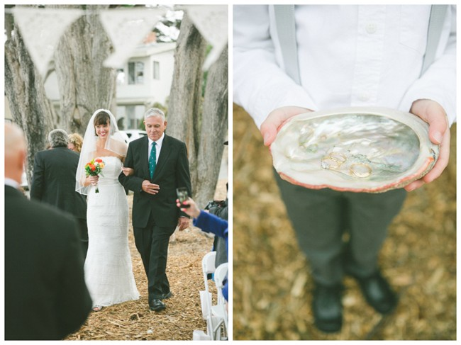 Bride walking down aisle with father and ring bearer holding oyster shell with rings