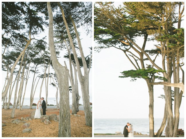 Bride and groom kissing under tall trees
