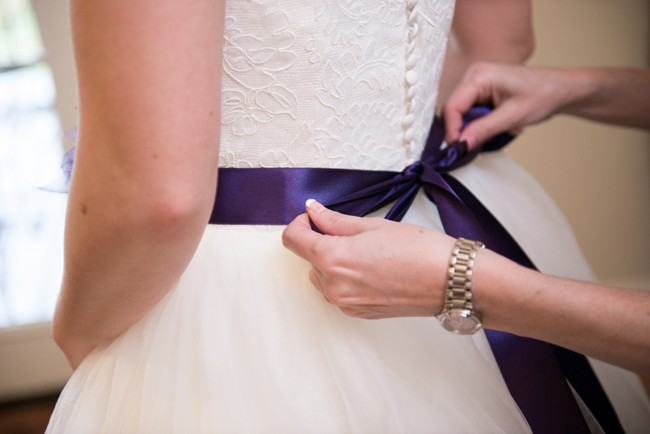 Purple sash being tied in a bow on wedding dress