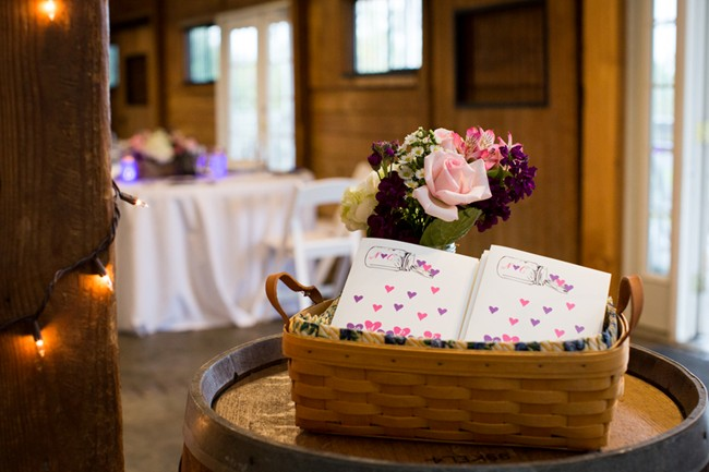 pink and purple flowers and wedding ceremony programs on wine barrel