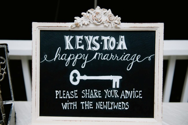 White ornate frame with chalkboard sign asking wedding guests to share their advice for the newly weds.