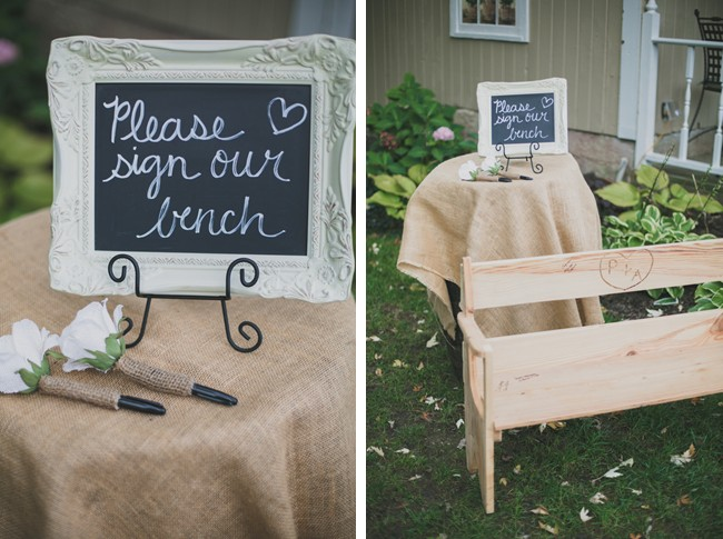 Chalkboard sign in a white ornate frame asking guests to sign the bench. Wood bench as a guest book.