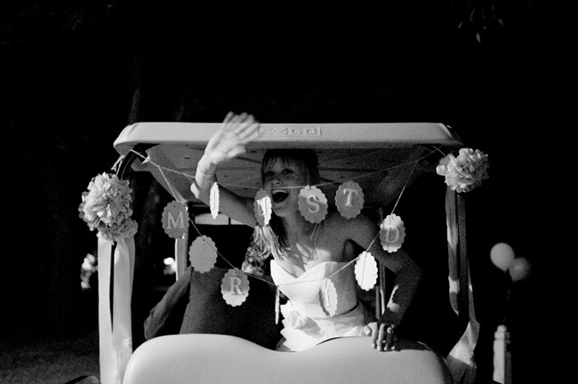 Bride and groom leaving wedding in a golf cart with just married sign