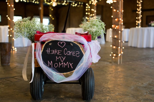 "Chalkboard sign on back of red wagon for flower girl with chalkboard sign saying ""here comes my mommy"""