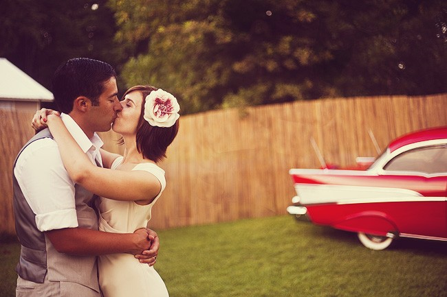 Bride and groom kissing in front of red vintage car