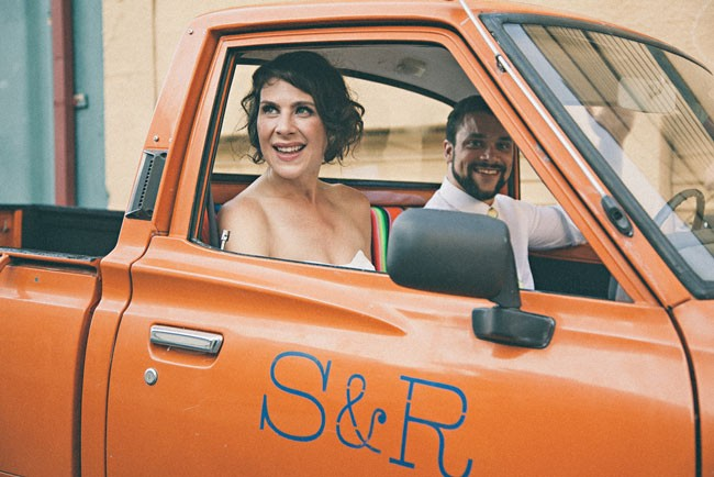 Bride and groom in an orange pick up truck